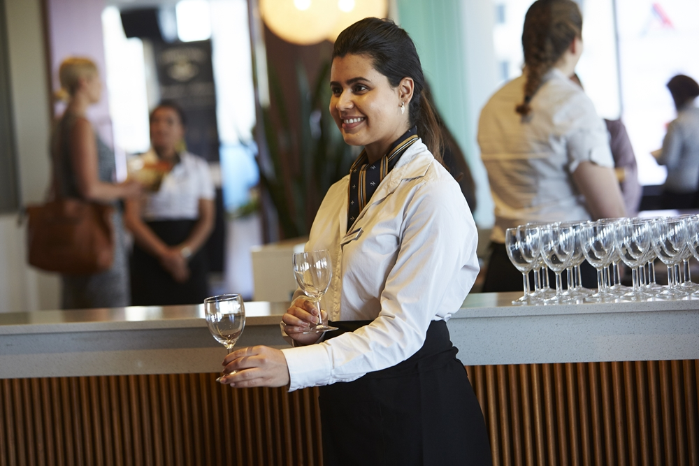 A Kenvale College student practices their waitressing skills.